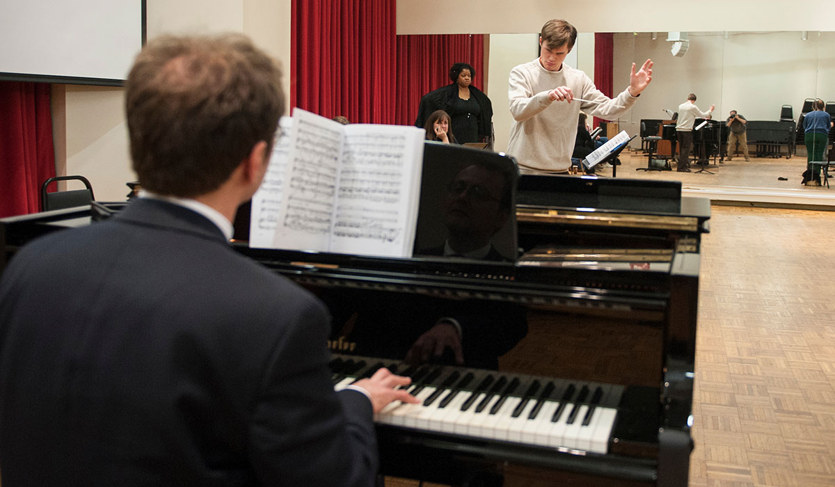 Man playing piano and student conducting