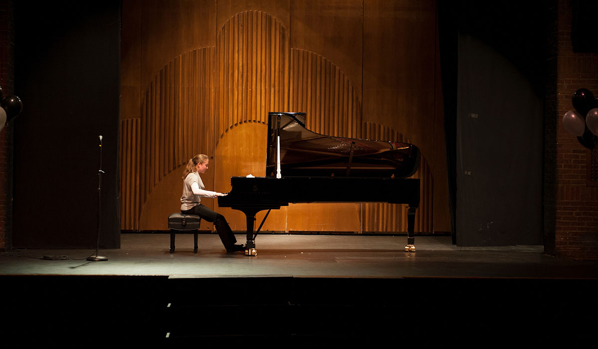 Student playing piano on stage